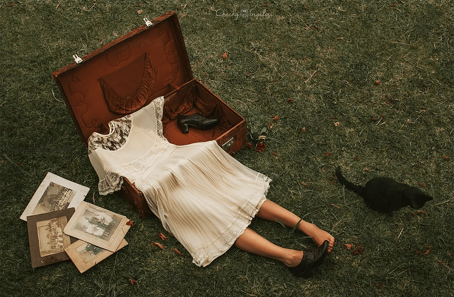 headless figure in a vintage suitcase