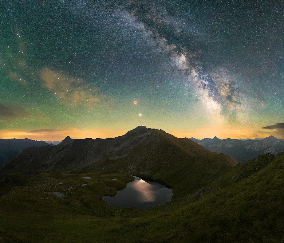 starry sky milky way over moutains and lake