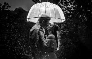 monochrome engagement photo of couple kissing under the rain