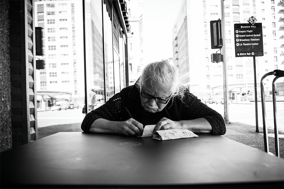 black and white image of an old woman sitting on a table in the street as she writes on a small piece of paper