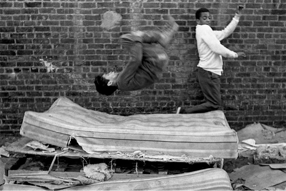 monochromatic film picture of two kids playing on mattresses in the street