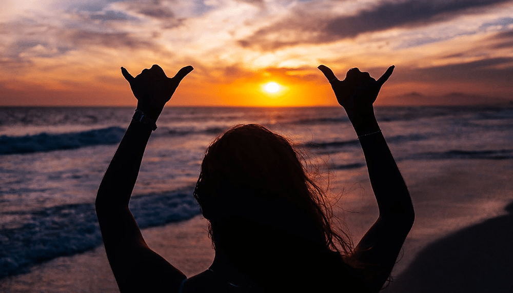 girl making the surf gesture on the beach during sunser