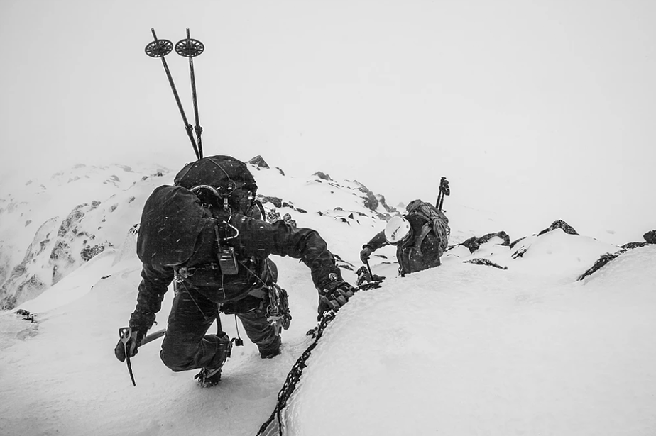 black and white photo of climbing skiers