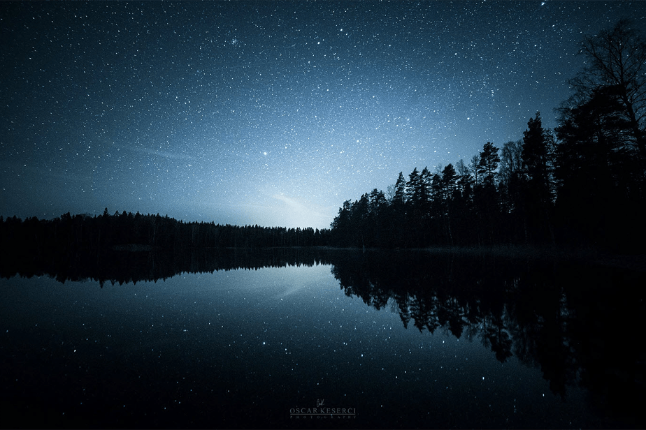 night photography stars reflected on a lake over a forest