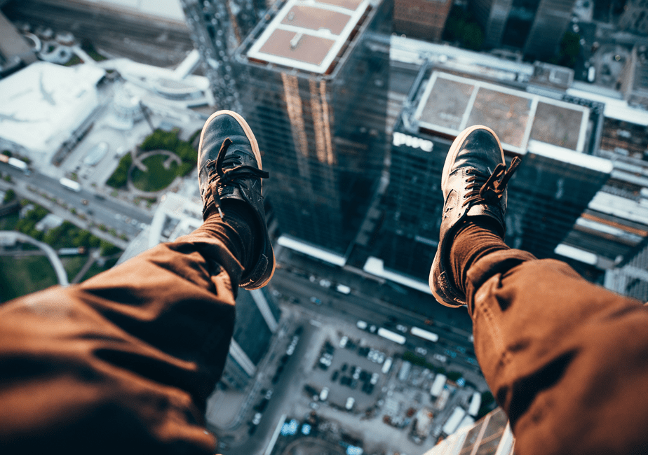 feet hanging out from tall tower in the city