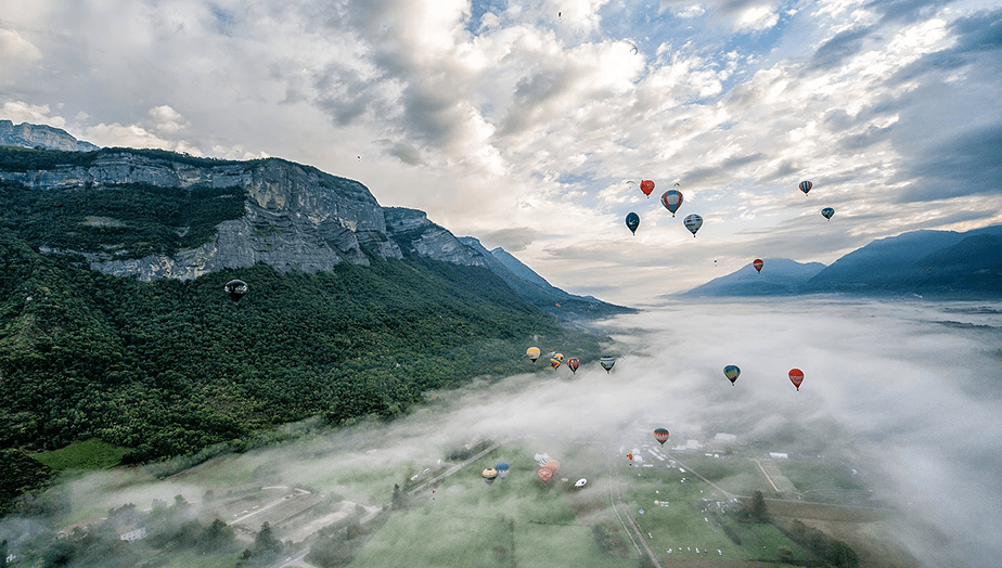 hot air balloons over foggy valley and mountains
