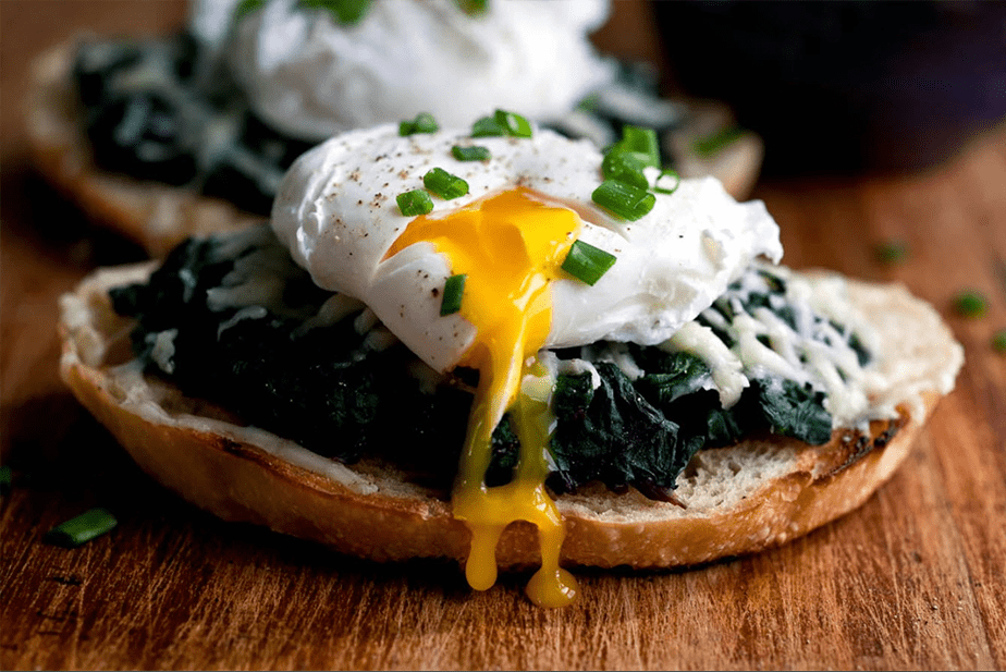 egg yolk dripping over spinach and bread