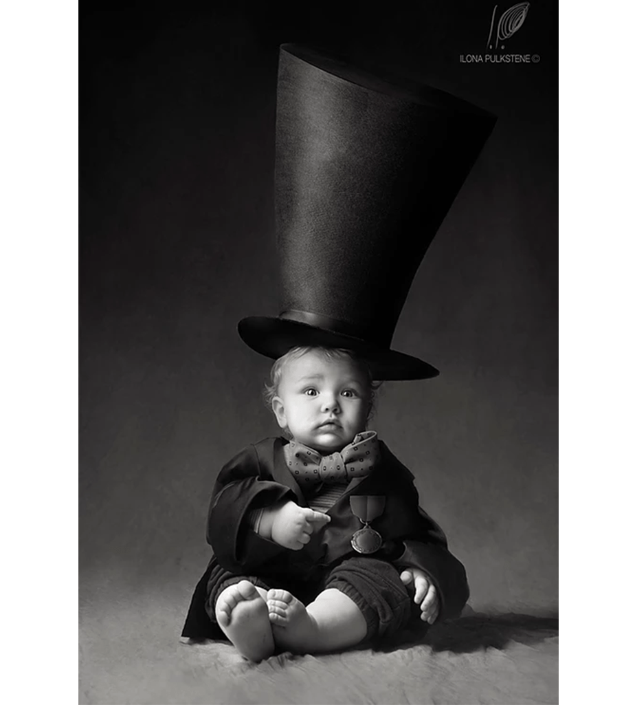 black and white photo of baby in a costume with a big hat