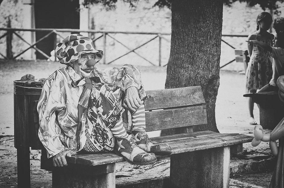 sad clown sitting on a bench by wix photographer Tuzlukova