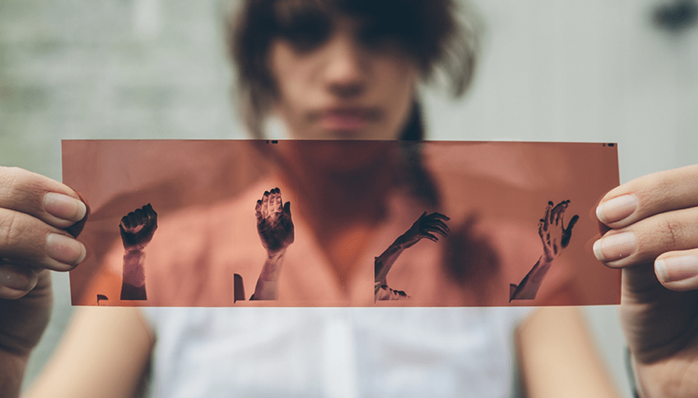girl holding a negative with photos of a hand