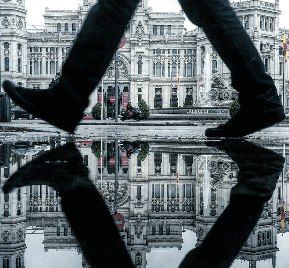 Reflection photo of a rain puddle with a person passing by