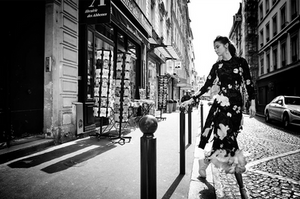 black and white photo of girl in floral dress waking in the street