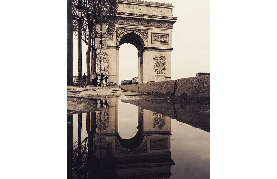 Reflection photo in Paris of the Arc de Triomphe mirrored in a rain puddle