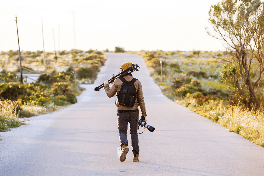 photographer walking on a field road with a tripod and camera
