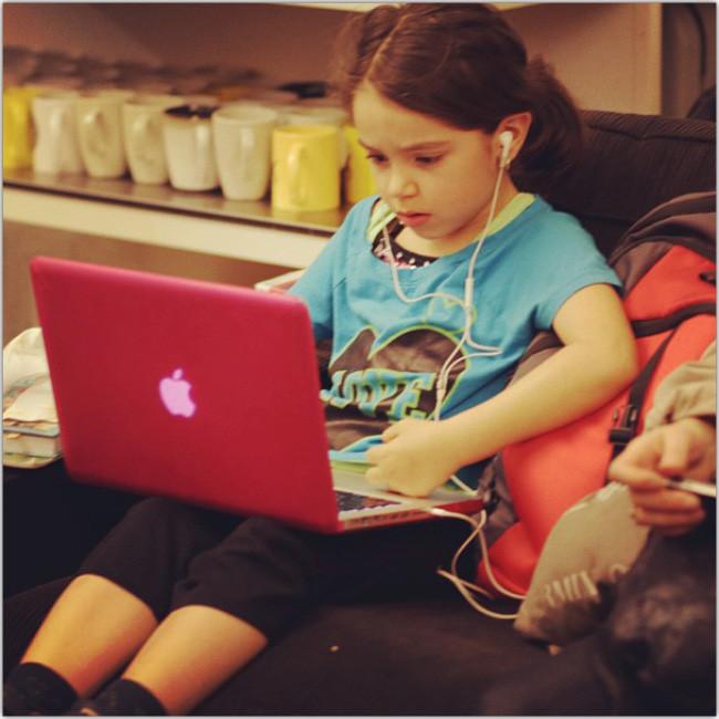 Niña pequeña usando un computador laptop rosado y ocupando audifonos.