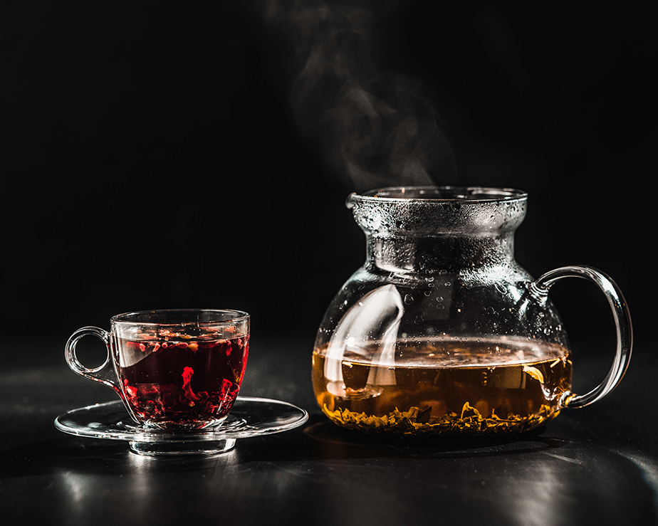 warm cup of red tea and green tea on glass kettle