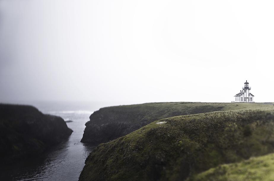 lighthouse on green cliffs