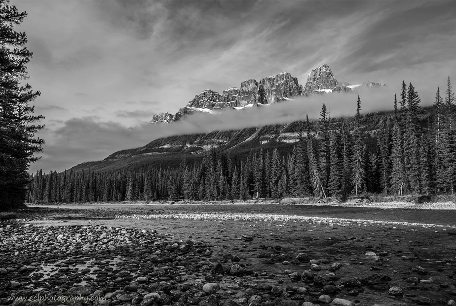 black and white landscape of a river passing next to a forest under cloud covered snowy mountains