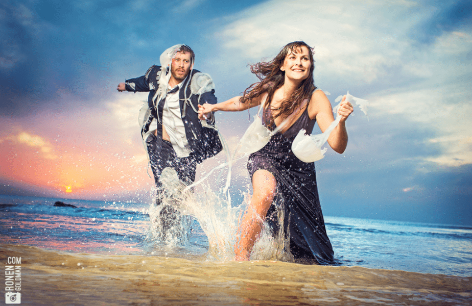 couple running on the beach with jellyfish