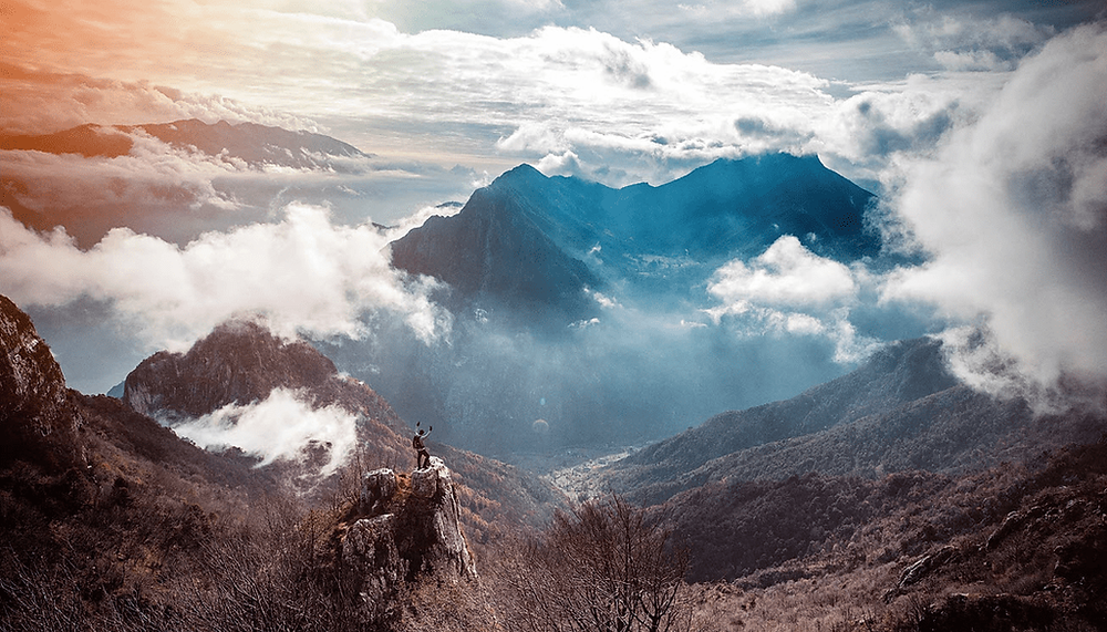 a person stands on a cliff overseeing the mountains and clouds