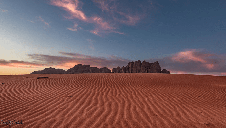 sunset over the red desert with rocky mountain formations in the horizon