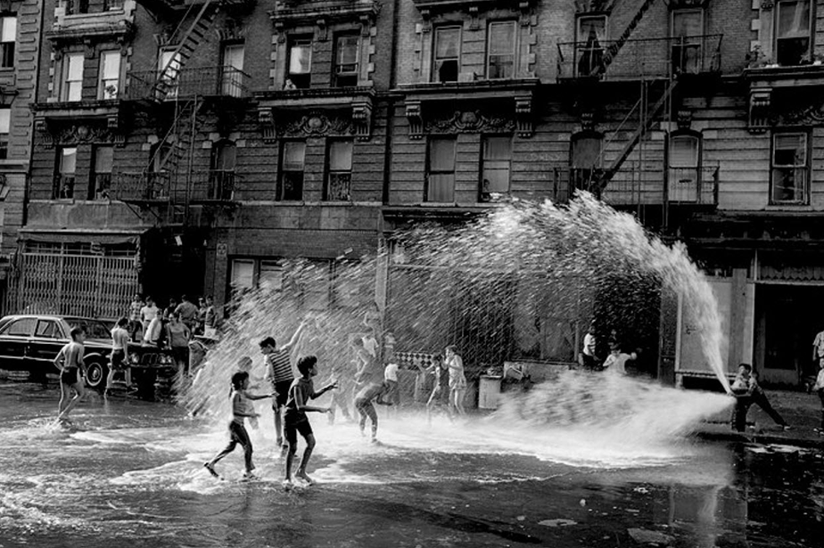 monochromatic film picture of kids playing with a fire hydrant in the street