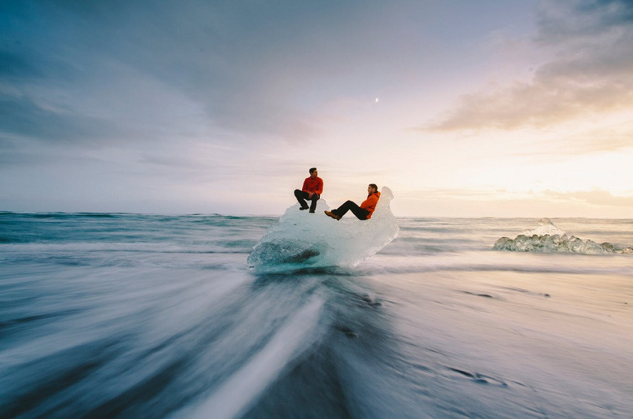 Two travelers sitting on a bloc of ice in the Arctic by Wix photographer Remy Brand