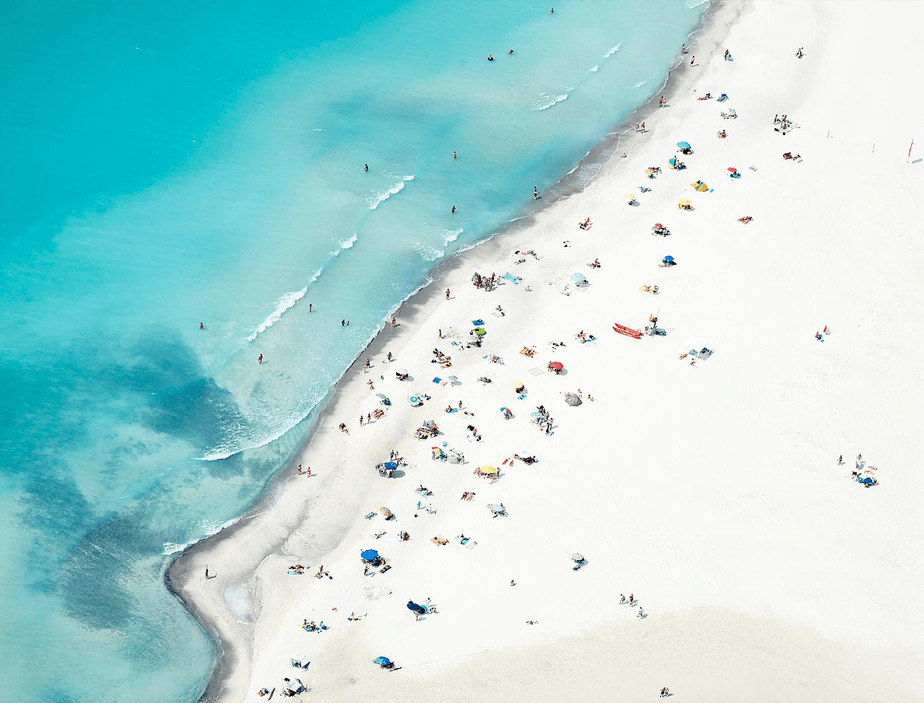 aerial photo of a beautiful white sand beach with clear blue water