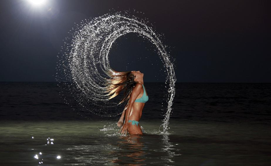 Girl with long hair splashing water.