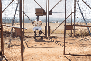 man sitting on a chair and reading a newspaper inside a gated area in a deserted field