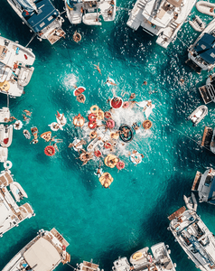 aerial view of people swimming on the sea with boats and floaties
