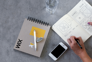 En una mesa está el block de notas de Wix, un vaso de agua, un celular y un block de diseño
