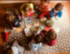 Bambini in cerchio sul tappeto, tra pupazzi e giochi