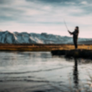 landscape photo of man fishing on river