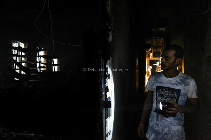 A man examines whats remains of his shop inside the market.