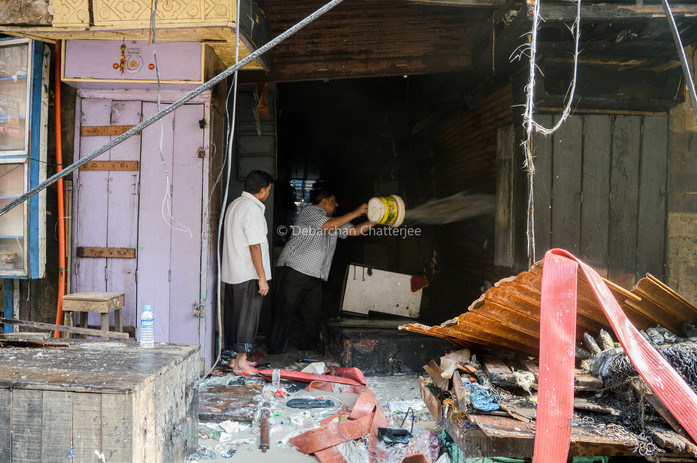 An owner trying to douse pocket fire inside his shop at bagree market.