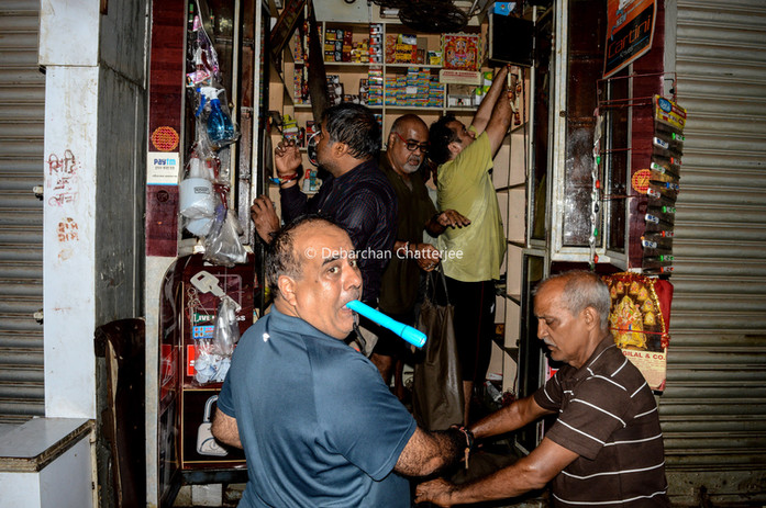 A shop owner clearing his shop which has not been touched by fire, a very few of the lucky ones inside the market.