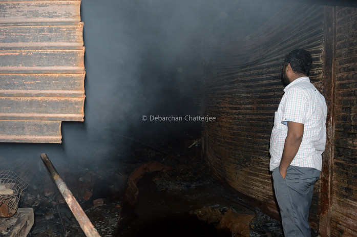 A man at the entrance of the market,looks ito the darkness of what the fire has left behind.