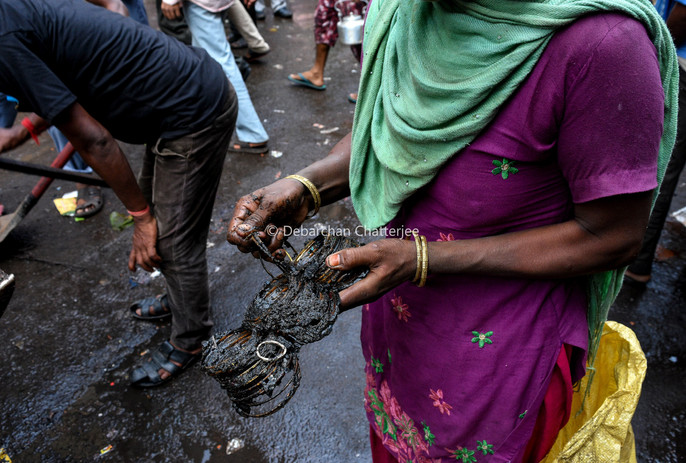 A lady with a burned collection of ornament bangles outside the market.