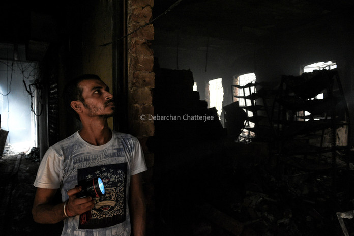 A man looking with a flashlight of what remains of his shop inside the market.