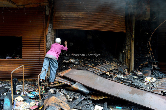 An old man checks whats left of his burned shop.