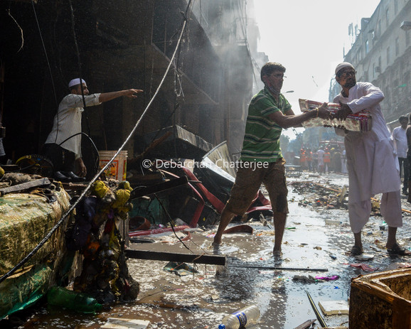 People evacuating unburned goods from the market as the fire retreats.
