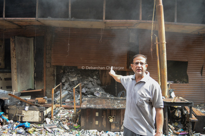 A man shows the remains of his burned shop.