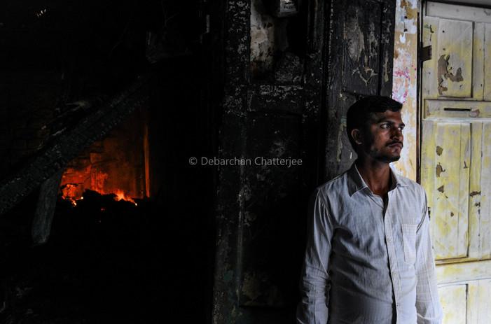 A man stands outside his burning shop inside Bagree market.