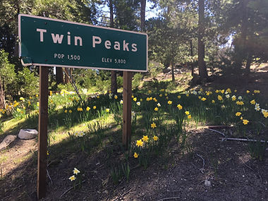 The town border and population sign for Twin Peaks, CA