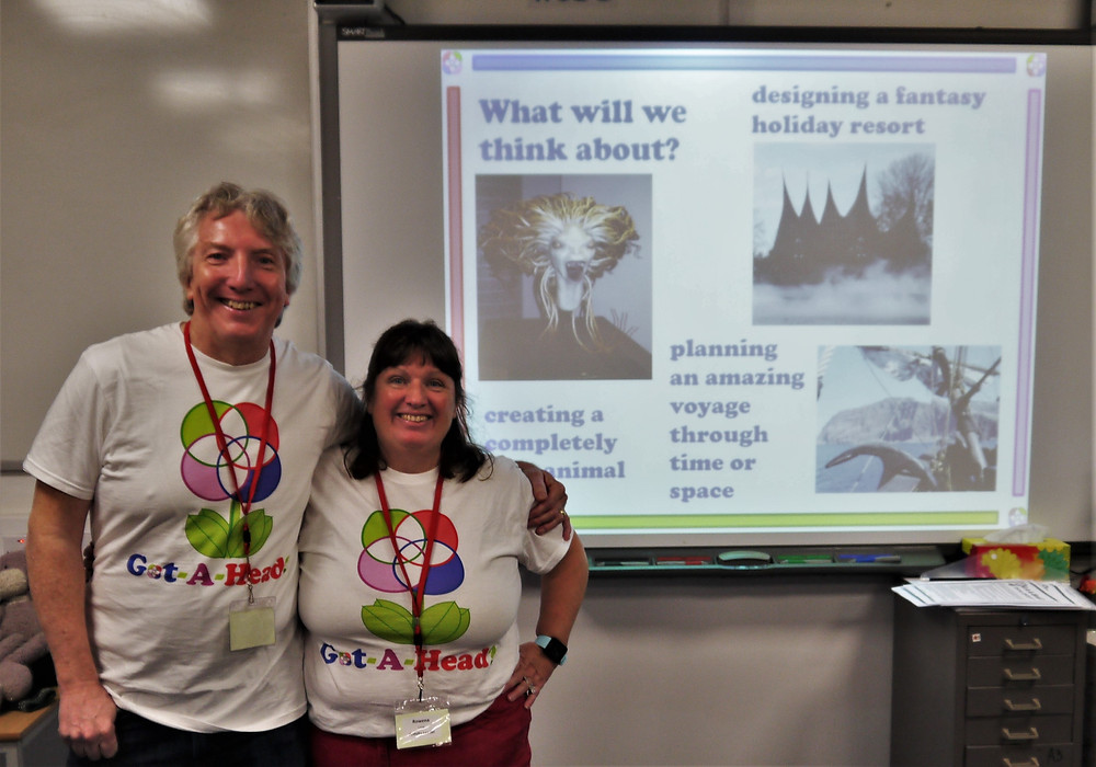 two presenters in front of a PowerPoint presentation