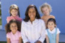 Teacher and children (3-5) smiling, fron