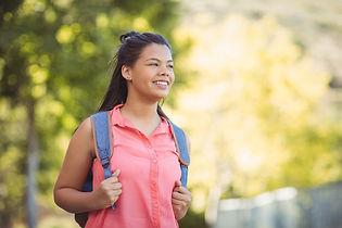 smiling-schoolgirl-standing-with-schoolb