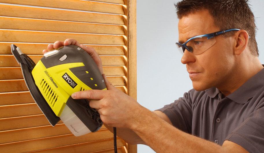 photo of man sanding wood