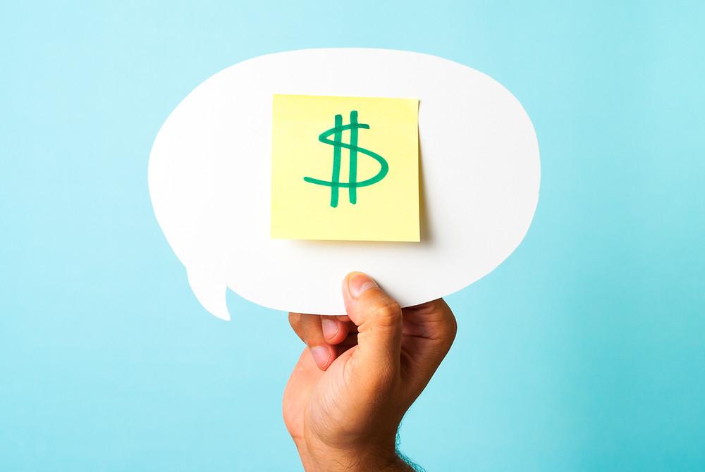 יד מחזיקה בועת דיבור עם פתק פוסט איט שעליו סימן של דולר